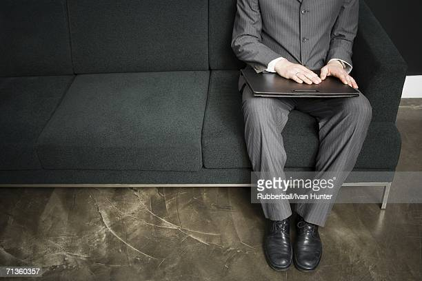 Low section view of a businessman sitting on a couch