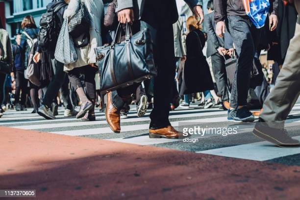 low section view of a crowd of busy commuters crossing street in shibuya crossroad, tokyo - japan commuters ストックフォトと画像