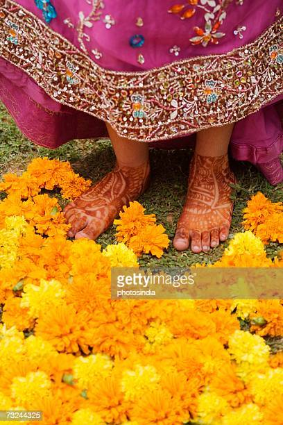 Low section view of a girl showing her henna tattooed feet with Marigolds in front of her
