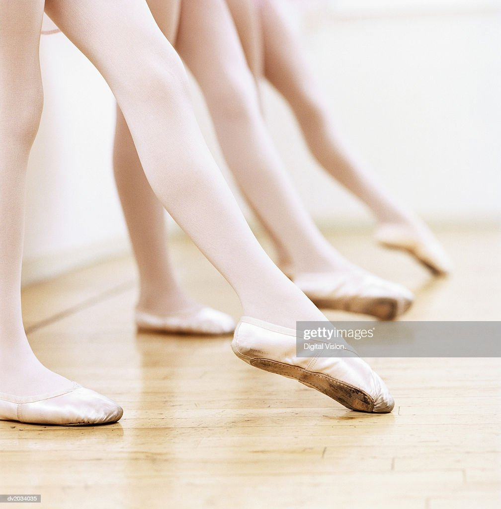 Low Section View of a Line of Female Ballet Dancers Practicing in the Dance Studio : Stock Photo