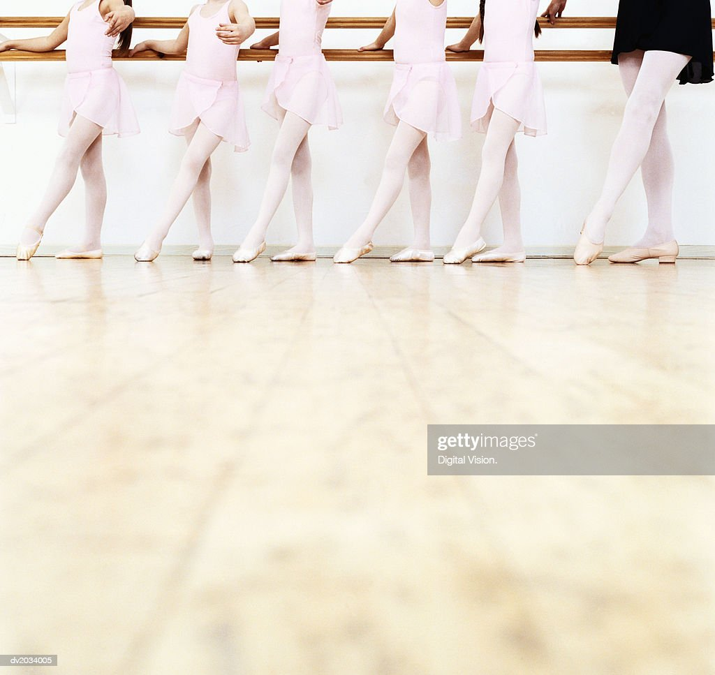 Low Section View of a Line of Young Ballet Dancers Practicing in a Dance Studio : Stock Photo