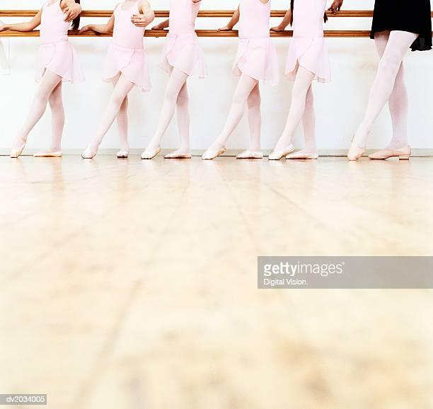 low section view of a line of young ballet dancers practicing in a dance studio - ballettstudio stock-fotos und bilder