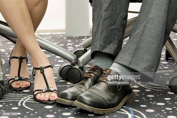 Low section view of a male and a female office worker playing footsie under a table