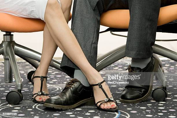 Low section view of a male and a female office worker playing footsie