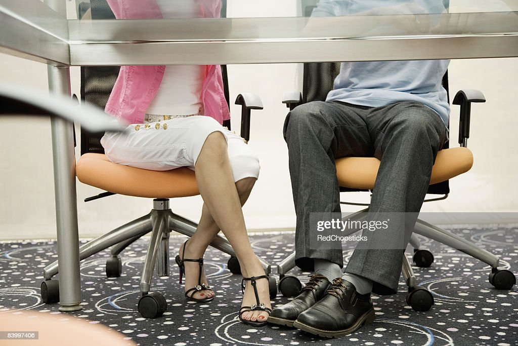 Low section view of a male and a female office worker playing footsie under a table : Stock Photo