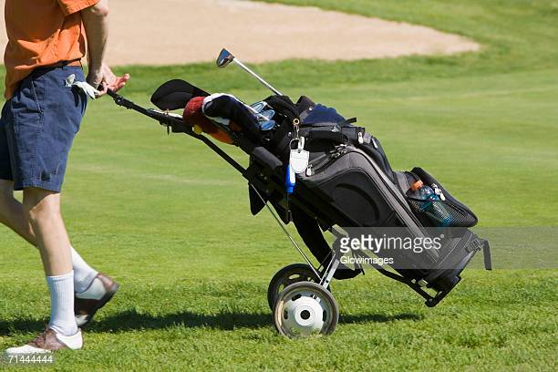 Low section view of a man pulling a golf bag