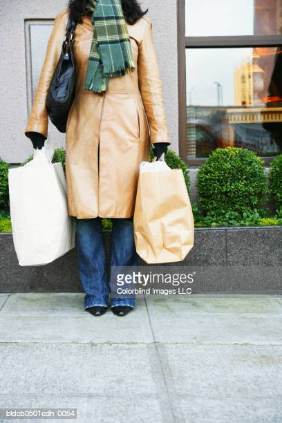 Low section view of a mid adult woman holding shopping bags