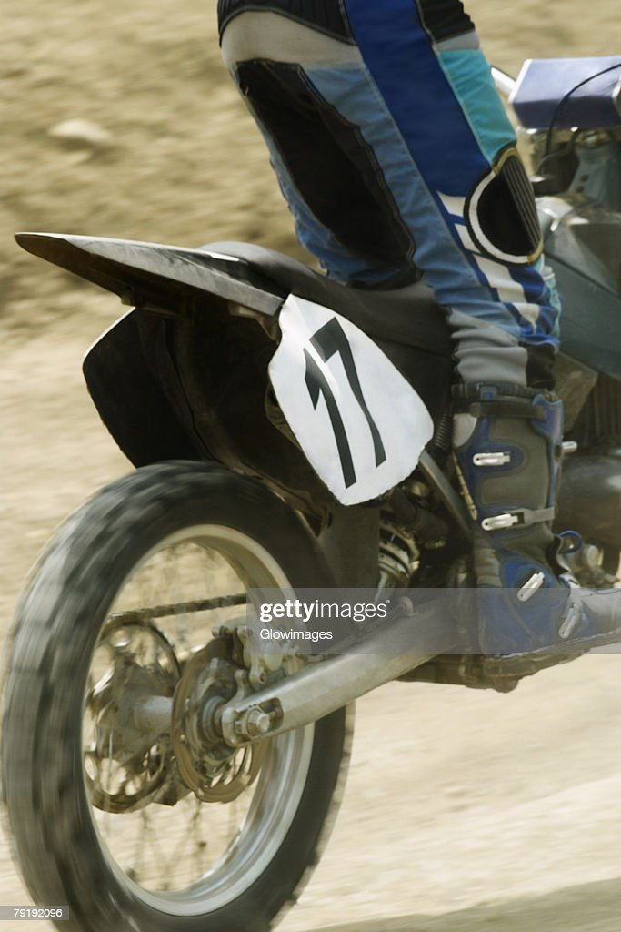Low section view of a motocross rider riding a motorcycle : Foto de stock