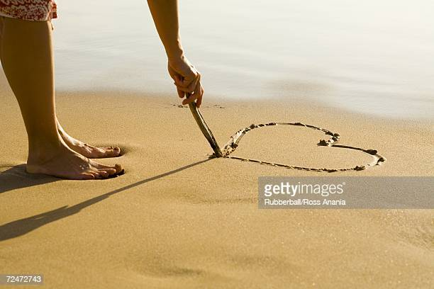 Low section view of a person drawing a heart in the sand on the beach