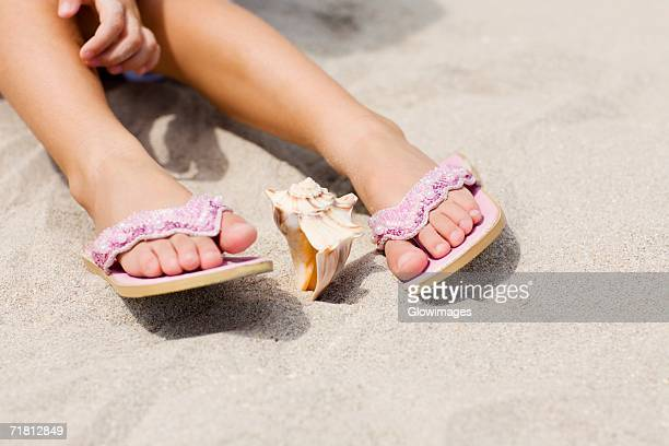 low section view of a person's feet near a conch shell - dead girl stock-fotos und bilder