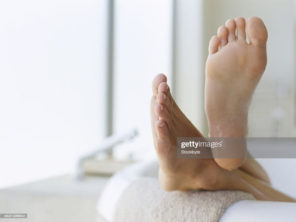 low section view of a person's feet resting on the edge of a bathtub : Stock Photo