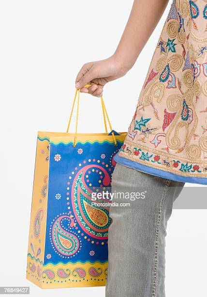 Low section view of a teenage girl holding a shopping bag