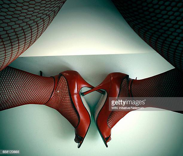 Low section view of a woman in red high heels and fishnet stockings simulating a heart shape with her legs