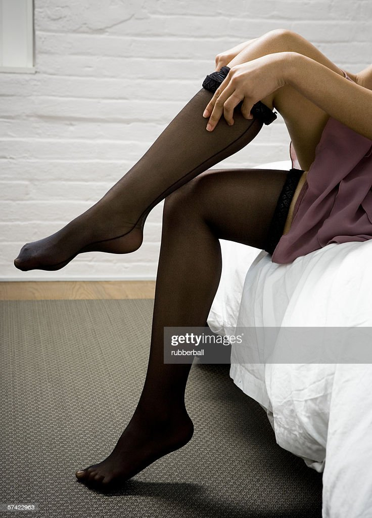 Low section view of a woman putting on stockings : Stock Photo