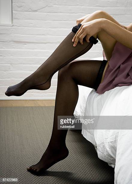 Low section view of a woman putting on stockings