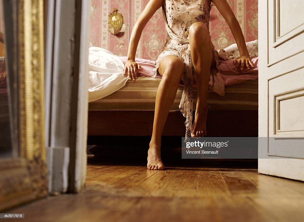 Low Section View of a Woman Sitting on a Bed : Stock Photo