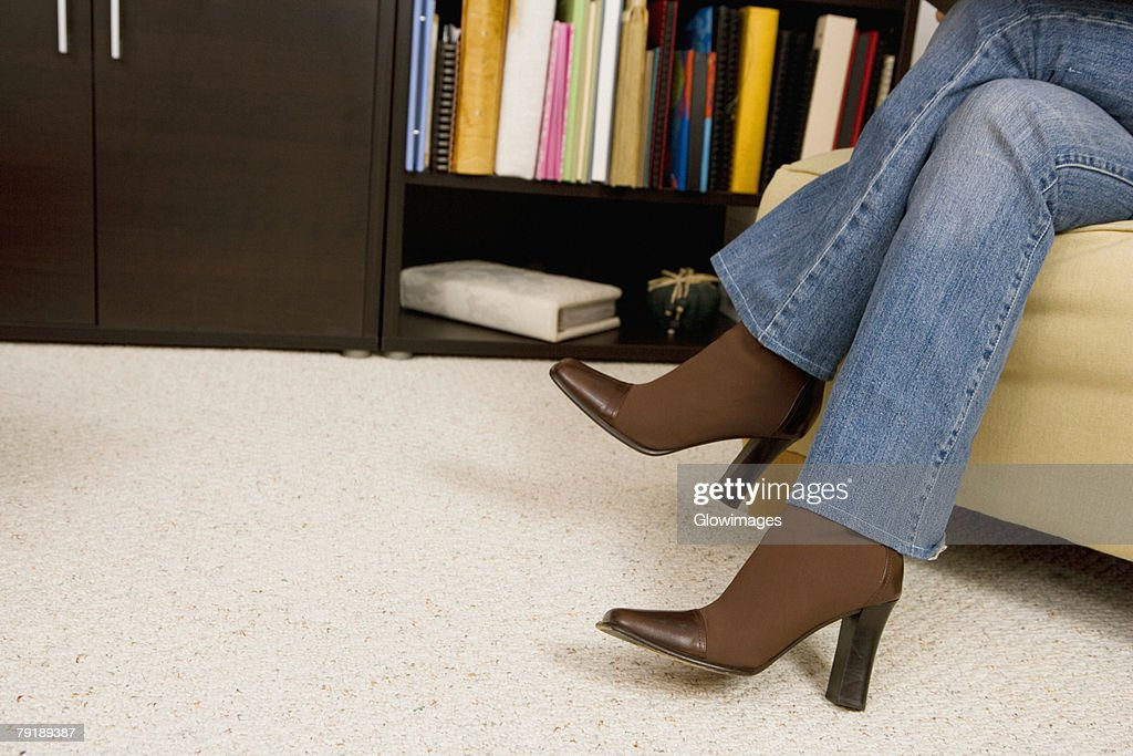 Low section view of a woman sitting on a couch : Foto de stock