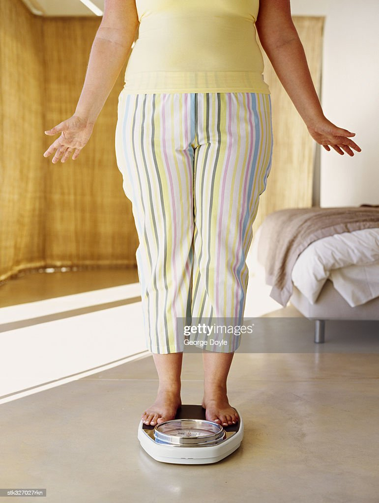 low section view of a woman standing on a weight scale : Stock Photo