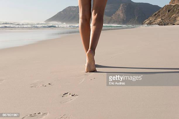 Low section view of a woman walking on the beach