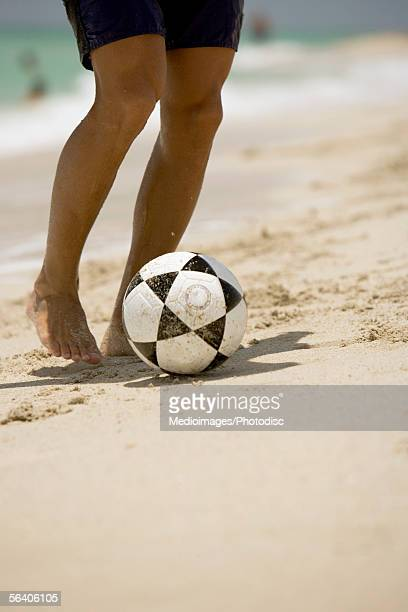 Low section view of a young man playing with a soccer ball on the beach