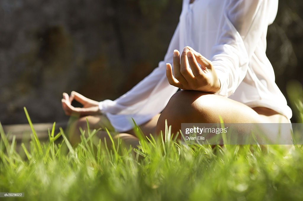 Low Section View of a Young Woman Sitting in the Lotus Position on the Grass : Stock Photo