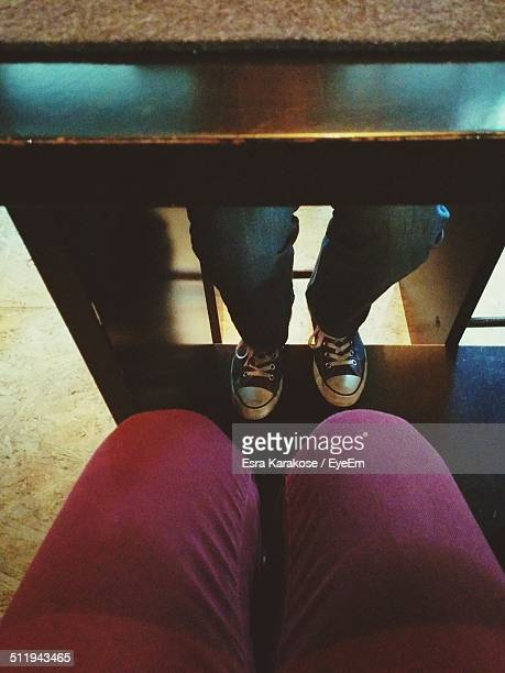 Low section view of couple under table in restaurant