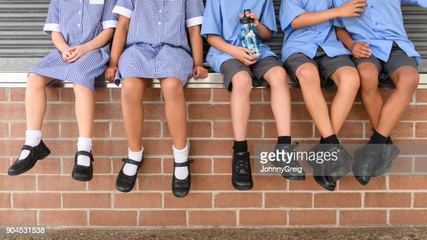 low section view of five school children sitting on brick wall wearing school uniform - school building stock pictures, royalty-free photos & images