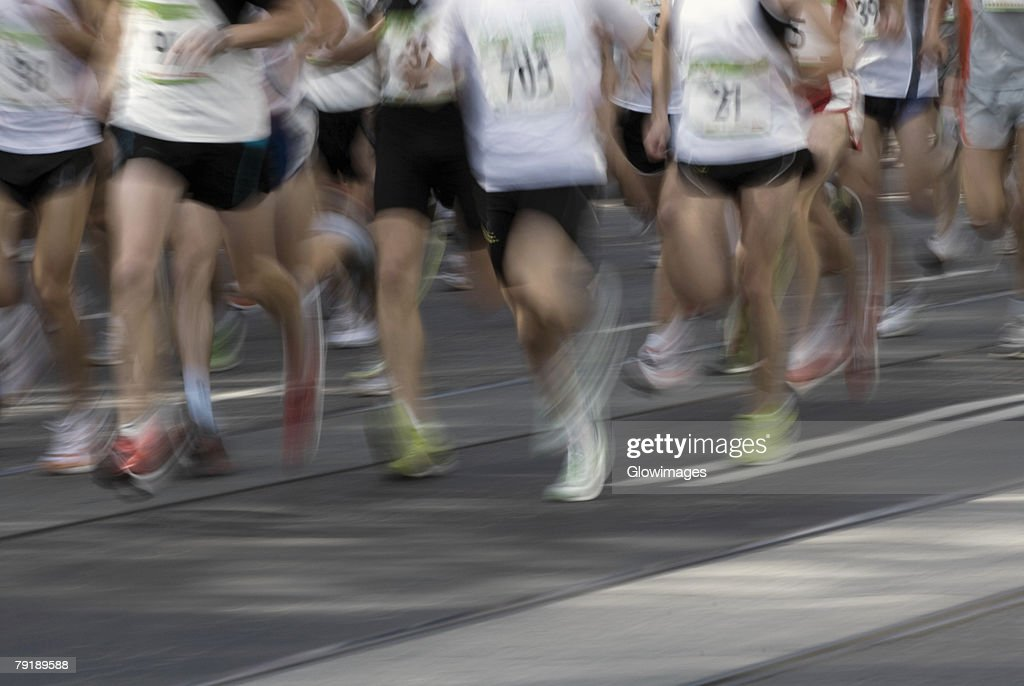 Low section view of male athletes running on a running track : Stock Photo
