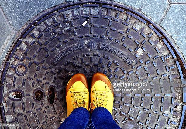 low section view of man standing on manhole - dirty feet stock pictures, royalty-free photos & images