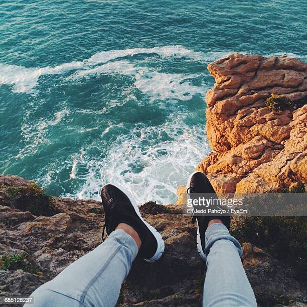 Low Section View Of Person Sitting At Coast