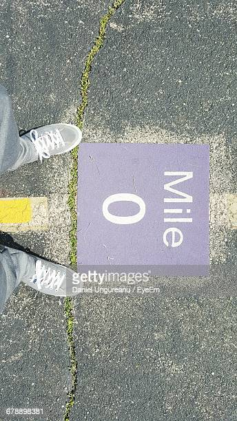 Low Section View Of Person Standing Near Mile Zero Sign