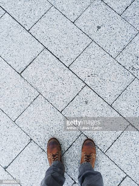 low section view of person standing on sidewalk - pavement stock pictures, royalty-free photos & images