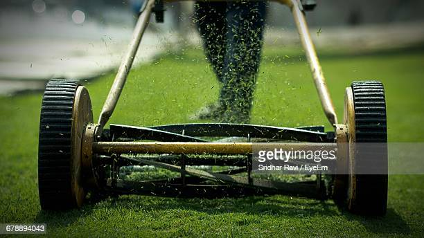 low section view of person using lawn mower - lawn mower stock pictures, royalty-free photos & images