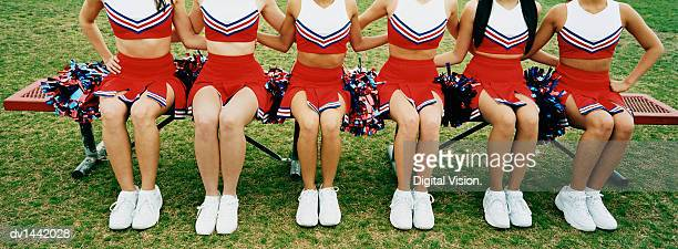 low section view of six cheerleaders sitting on bench arm in arm - black cheerleaders stock photos and pictures