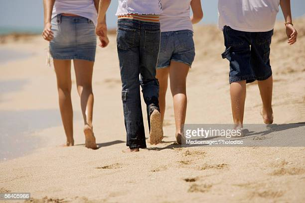 low section view of three girls and a boy walking on the beach - girls with short skirts - fotografias e filmes do acervo