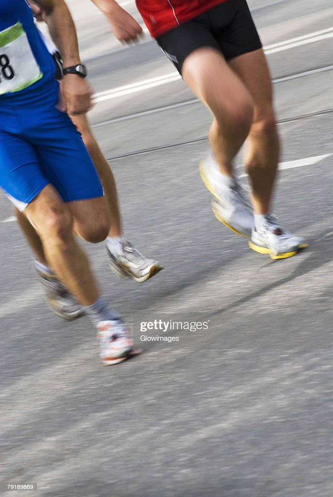 Low section view of three male athletes running on a running track : Stock Photo