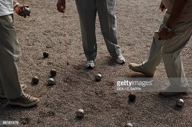 Low section view of three people playing petanque AlpesMaritimes France