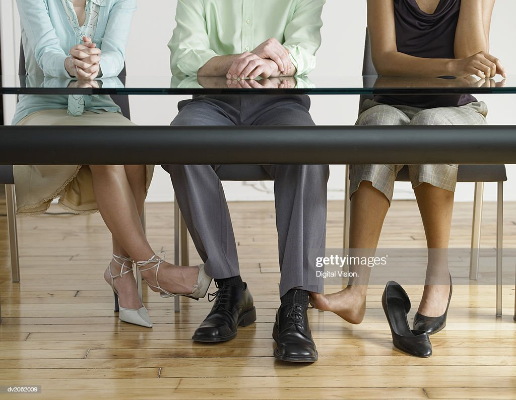 Low Section View of Two Businesswomen Touching the Feet of a Businessman Under a Table : Stock Photo