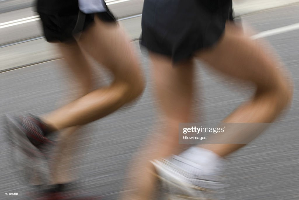 Low section view of two male athletes running on a running track : Foto de stock