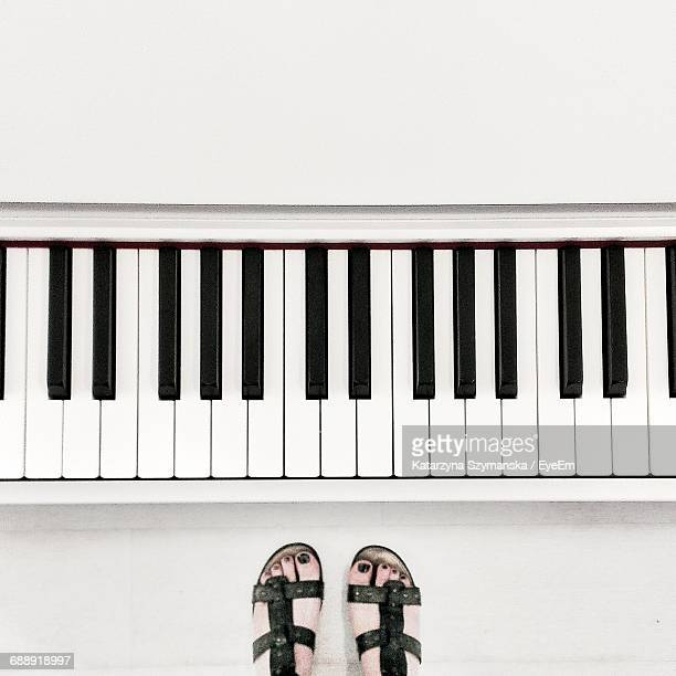 low section view of woman standing by piano - keyboard instrument stock photos and pictures