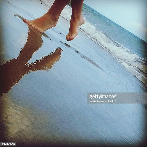 Low Section View Of Woman Walking On Beach