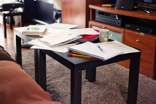 low table in the room full of books, sheets and study notes strewn over it - paper clutter stock pictures, royalty-free photos & images