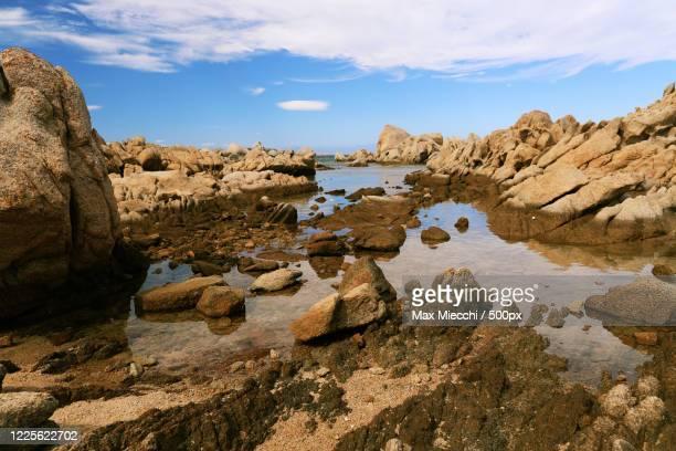 low tide at the rocky beach in la maddalena, italy, sardinia - max miecchi foto e immagini stock