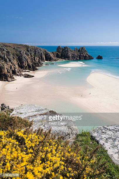 low tide reveals a white sandy beach at porthcurno looking towards logans rock. - porthcurno stock pictures, royalty-free photos & images