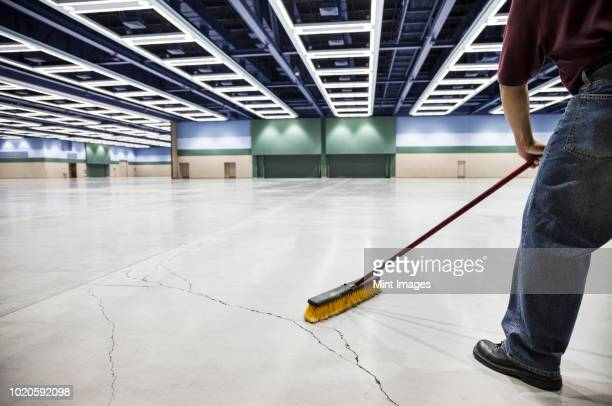 A low view closeup of a man sweeping the floor of a convention centre arena.
