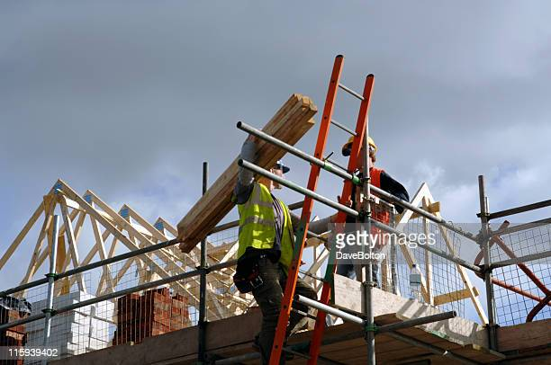 Low view of two construction workers on top of house frame