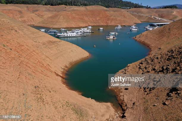 Low water levels are visible next to houseboats that sit anchored at the Bidwell Canyon Marina on Lake Oroville on June 01, 2021 in Oroville,...