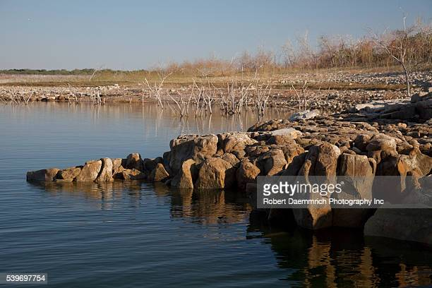 Low water levels caused by a continued drought expose rocks and brush on the United States side of Falcon Lake on the Texas-Mexico border south of...