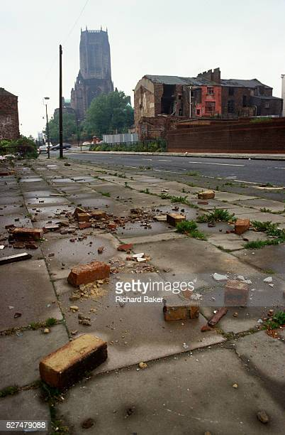 Low, wide landscape of dereliction and poverty during the early 1990s in the city of Liverpool, England. The Catholic cathedral rises high in the...
