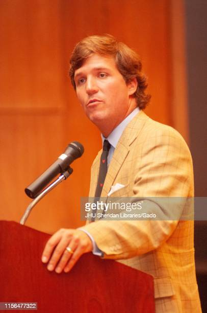 Low-angle close-up of political commentator Tucker Carlson, speaking from a podium during a Milton S Eisenhower Symposium at the Johns Hopkins...
